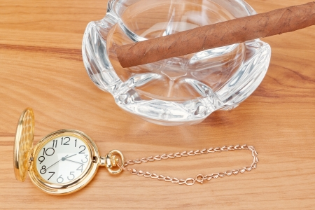 Retro image of gold pocket watch and a Havana cigar in the ashtray. In the warm yellow tones. Stock Photo - 19689836