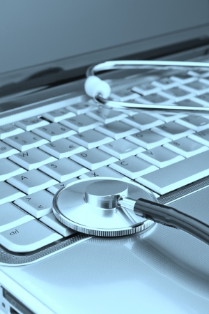 Modern laptop and stethoscope to diagnose problems close up. On a white background. photo