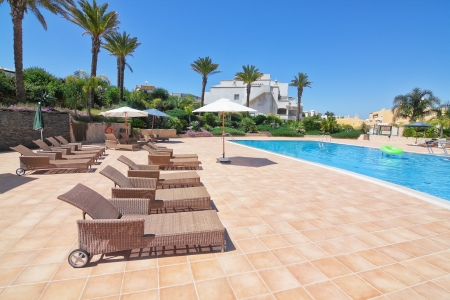 Summer day in the pool with sunbeds and parasols. Portugal Algarve.