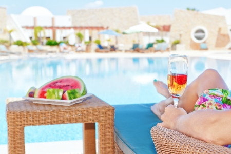 Girl with a glass of champagne and snacks watermelon. Against the background of the pool.