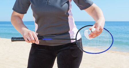 Una ni�a juega al b�dminton en la playa. Close-up. photo