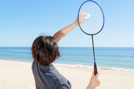 The girl on the beach serves playing badminton. Close-up. photo
