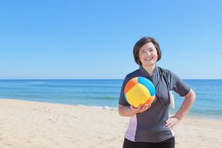 Middle-aged woman on the beach with a volleyball ball. Close-up. photo