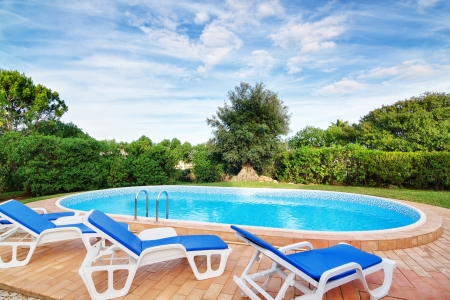 sunbeds: Luxury swimming pool with sun loungers. For relaxation and swimming. Summer. Stock Photo