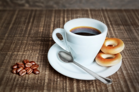 A cup of coffee with baked cracknels, bagels. Coffee beans on the wooden background. photo