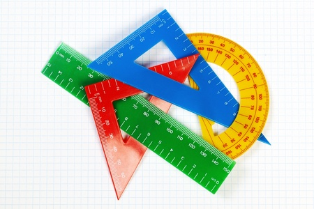 Protractor ruler and items for school and education. On a sheet in a cage for mathematics. photo