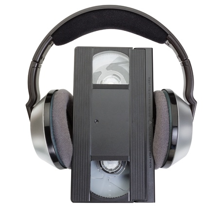 vhs videotape: An old classic videotape VHS and wireless headphones. Stock Photo