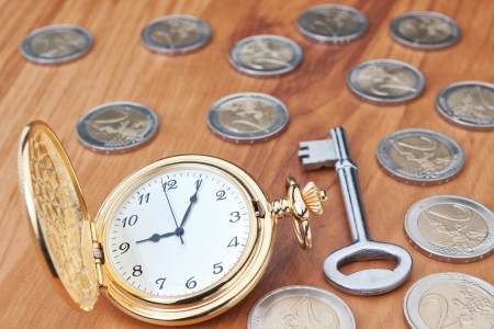 Vintage pocket watch and a key against the euro coins. Close-up. photo