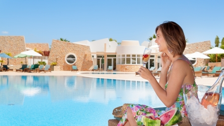 Girl with a glass of champagne by the pool. In the summer on vacation. photo