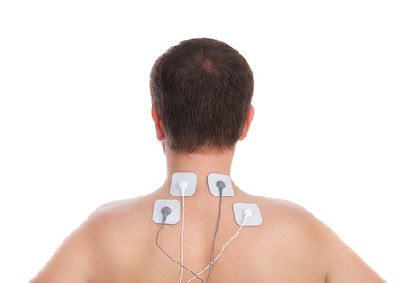 Man with problems in the neck and in the spine massage makes electrostimulator. photo