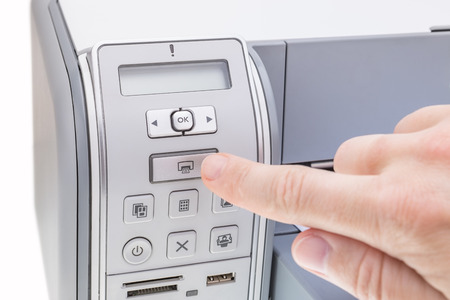 Office worker presses the button the printer. Close-up. photo