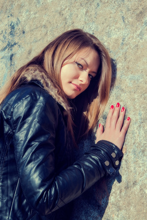 Portrait of blonde attractant in leather jacket. In vintage color solution. photo
