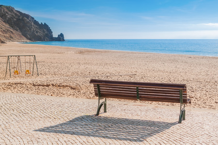 Secluded place for meditations on the sea shore. On a bench near the swing. photo