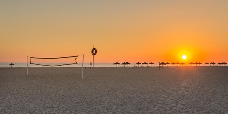 Wonderful summer sunset at the beach volleyball court. Portugal holiday. photo