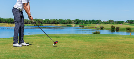 Man simulates play golf. With the stick on the green field.