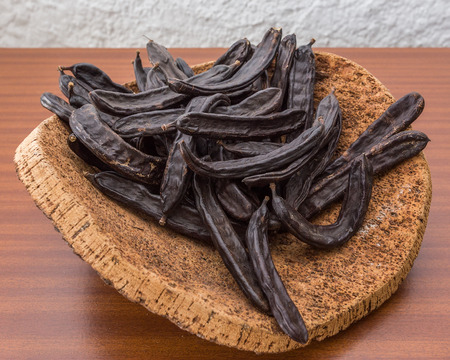 cortical: Carob pods on cortical stand. On the table.