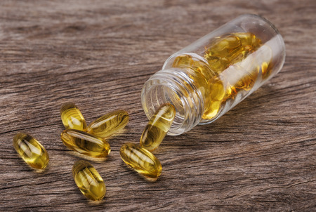 tank fish: Tablets vitamin E in a glass tank. Fish oil. Stock Photo