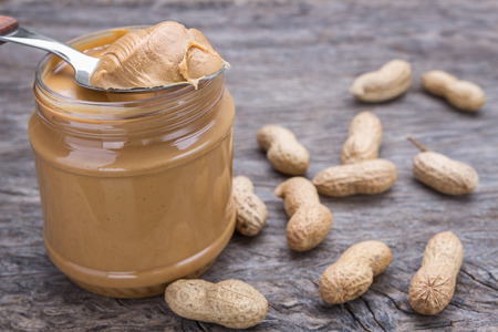 Jar of peanut butter with nuts. On wooden texture. Archivio Fotografico