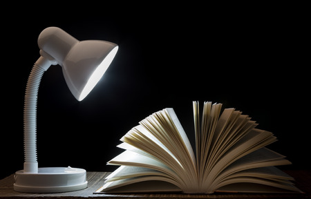 Lamp night light on the book. For reading. In library. photo
