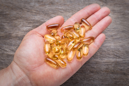 vitamin d: Hand holding pills for healing health. Close up.