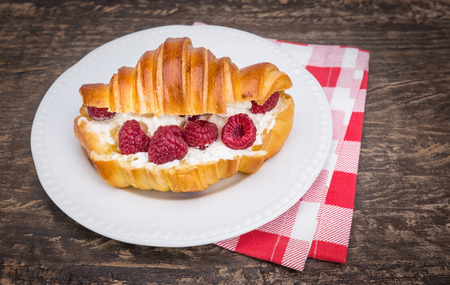 butterfat: Delicious croissant with cream and raspberries. For breakfast. Stock Photo