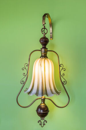 wall sconce: Ancient vintage luminaire. On the green wall.