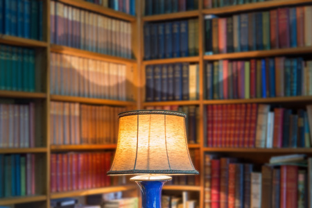 law library: Angle library of old books and knowledge. The lamp shade in the foreground.