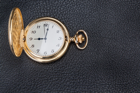 Gold pocket watch on a textured skin. Close-up. photo