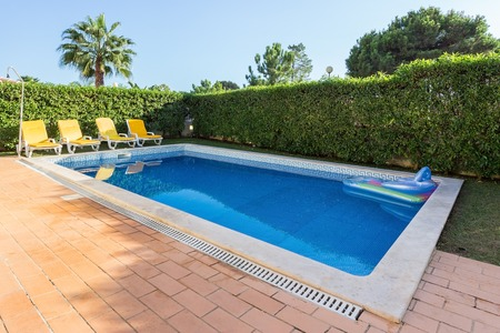 Home swimming pool in the summer. Sunbeds for leisure travelers.