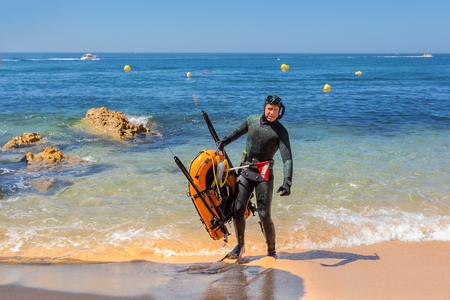 speargun: Underwater hunter in flippers preparing to dive. Underwater fishing in the Atlantic Ocean. Stock Photo