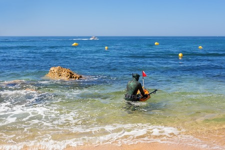 speargun: Underwater hunter in the water preparing to dive. Underwater fishing in the Atlantic Ocean. Stock Photo