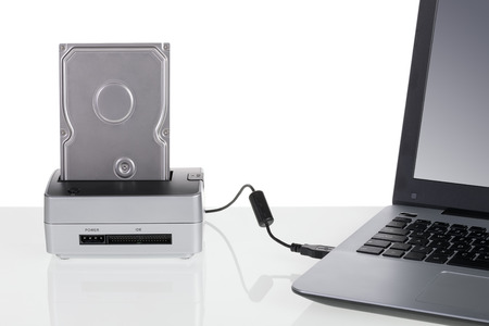 portable hard disk: Hard disk drive with docking station connected to a laptop computer. For data storage.
