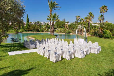 venue: Decorations for the wedding ceremony in the garden. With white chairs.