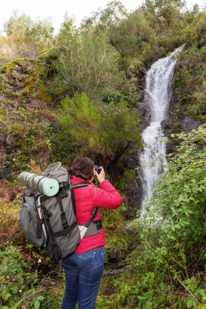 monchique: Girl tourist photographing a waterfall. In Portugal, the village Monchique. Stock Photo
