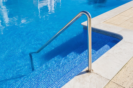 handrails: Detail of the steps of the pool. Handrails of metal.