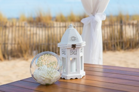 wedding table decor: Details of objects on the wedding ceremony. Candle light bouquet. Stock Photo
