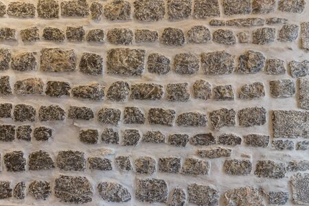 overbuilding: Horizontal stone wall texture close up. Lacquered.