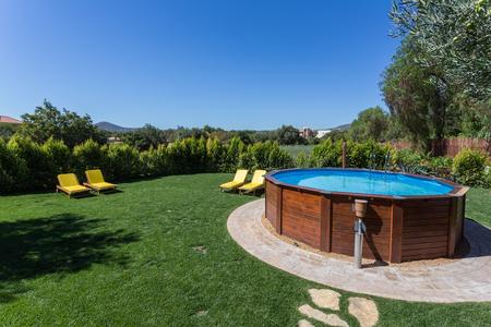 Una piscina sobre tierra coloca en una plataforma de concreto en el patio trasero en un día soleado de verano.