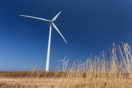 generators: Wind generators, below, the grass in the foreground. Portugal Stock Photo