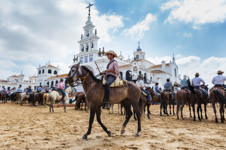 baptized: El ROCIO, ANDALUCIA, SPAIN - 26 JUNE 2016: Young boy rider guides horse to be baptized. Facing the Church.
