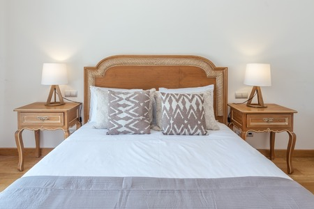 bedside: Married wooden bed in bedroom with modern decoration.