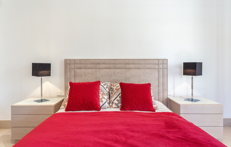 bedroom design: Stylish modern bedroom with bed and red pillows.