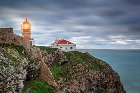 Lighthouse shines out to sea ships. Sagres Cabo Sao Vicente