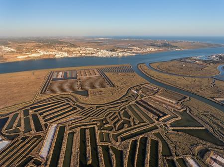 Aerial. Textured fields of swampy salt lakes. Salines of Portugal. Vila Real Santo Antonio. Stock Photo