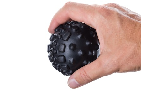 Hand holding a ball with spikes for myofascial massage. On white background.
