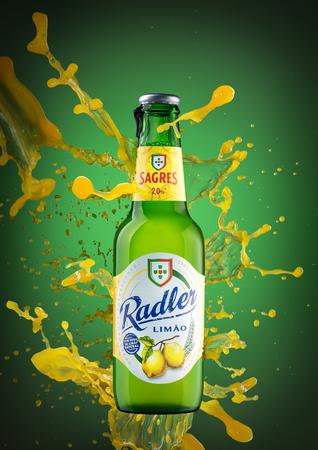 Portugal Faro ,3 Novembro 2017. Spray a splash of juice on a bottle of drink. On green background.