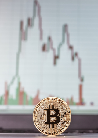 Coin Bitcoin close-up, and schedule the exchange in background. Stok Fotoğraf