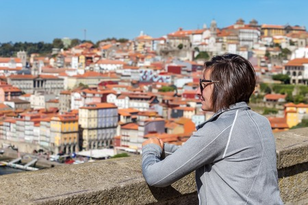 The girl on the bridge of San Luis in the Portuguese city of Porto. Looks at the landscape.