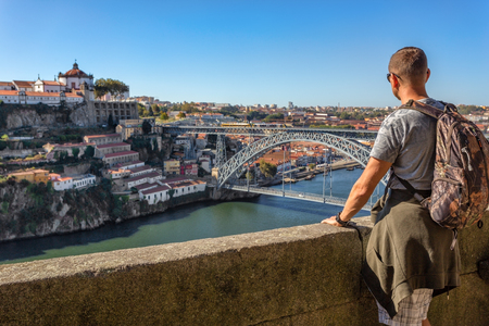 A young man admires the scenery of Porto, the Douro River. View of the bridge of San Luis. 免版税图像