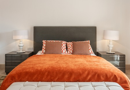 Dormitorio de estilo moderno con cama y almohadas. Vista frontal.